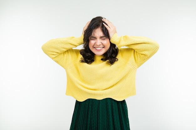 Alegre menina morena feliz em uma camisola amarela e saia verde sobre fundo branco
