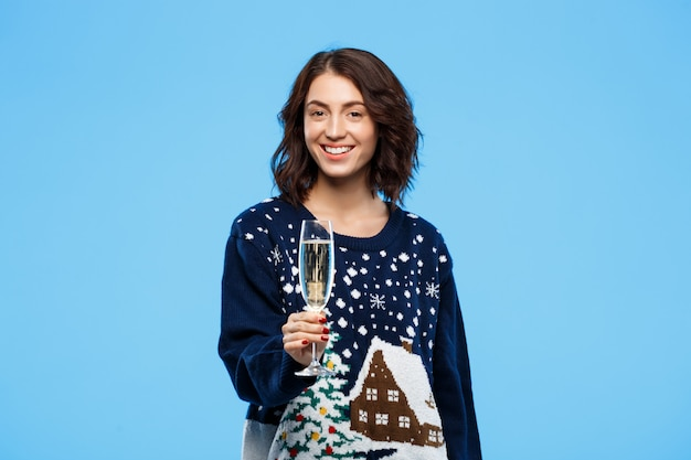 Alegre menina morena linda alegre camisola de malha aconchegante sorrindo segurando copo de champanhe sobre parede azul