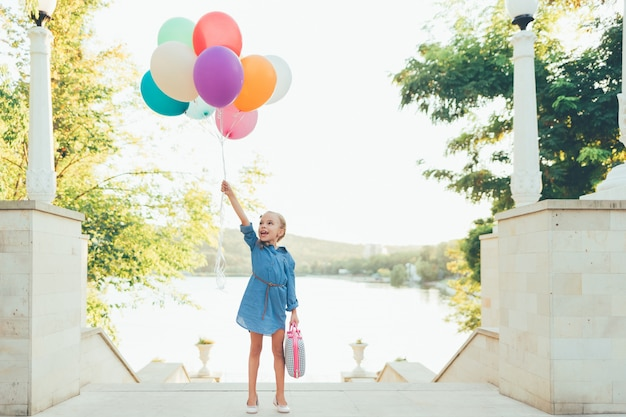 Alegre menina segurando balões coloridos e mala infantil
