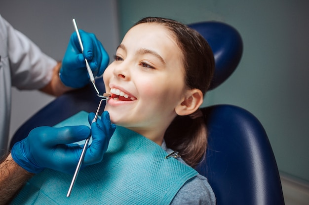 Alegre menina sentada na cadeira odontológica na sala