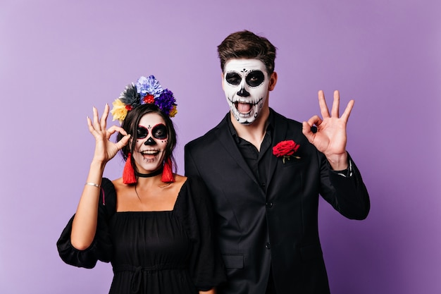 Alegre menino e menina de cabelos escuros sorriem e mostram sinal ok. retrato de feliz senhora mexicana e homem com rostos pintados.