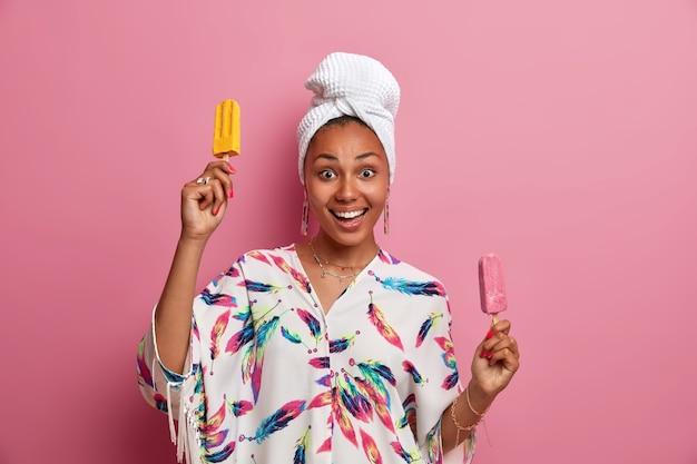 Alegre modelo feminina de pele escura segurando dois deliciosos sorvetes e danças