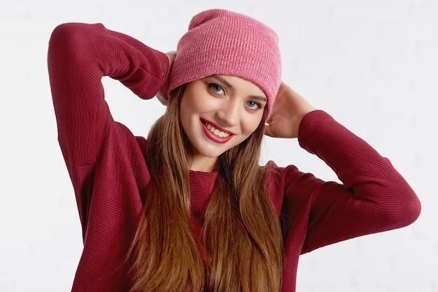 Alegre modelo linda no chapéu vermelho e camisola com maquiagem de olhos e batom vermelho