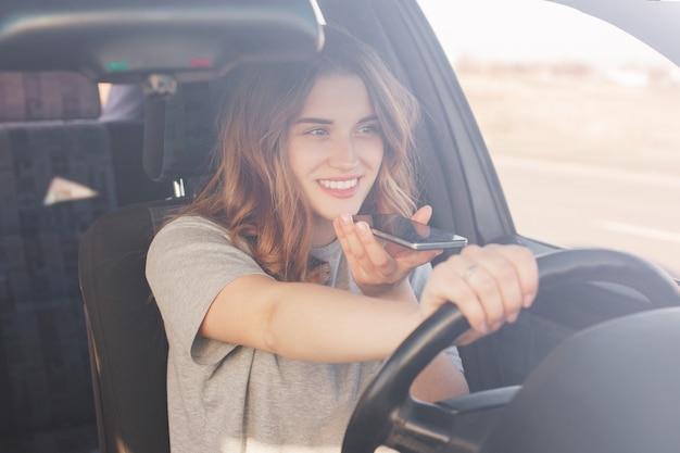 Alegre motorista do sexo feminino estar de bom humor, tem uma longa viagem em seu automóvel favorito, gosta de música agradável e maravilhosa vista pela janela, gosta de dirigir. jovem encantada goza de alta velocidade