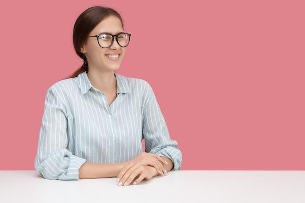Alegre muito jovem gerente feminina de óculos, rindo de uma piada ou situação engraçada, se divertindo no trabalho, sentado à mesa. expressões faciais humanas positivas, emoções, reações e sentimentos
