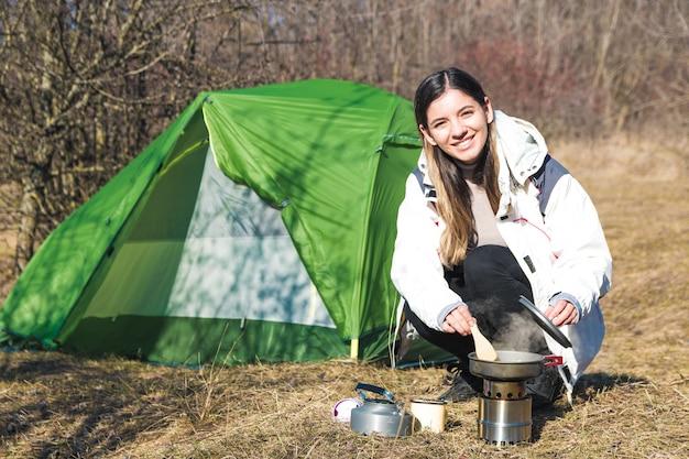 Alegre mulher acampar sozinho cozinhando na frente de sua barraca. tempo para o ar livre