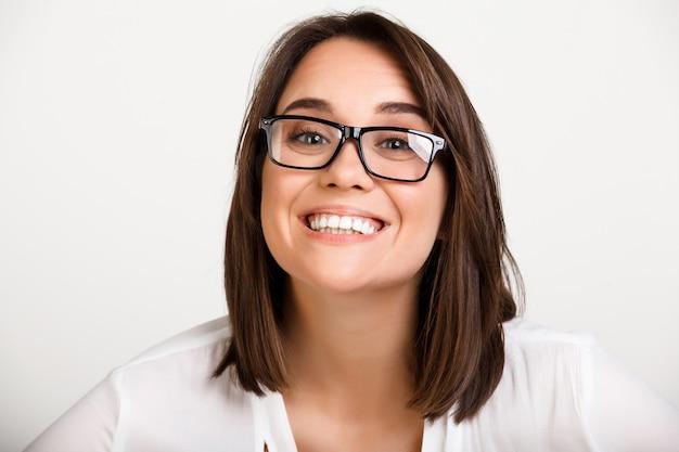 Alegre mulher adulta em copos, sorrindo toothy