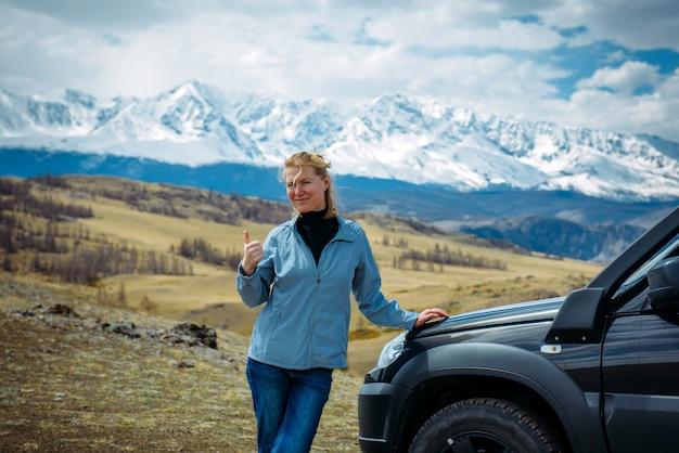 Alegre mulher adulta sorridente fica em uma colina perto do carro contra a cordilheira coberta de neve. viajante da mulher ao ar livre em um dia ensolarado, aparecendo o polegar.