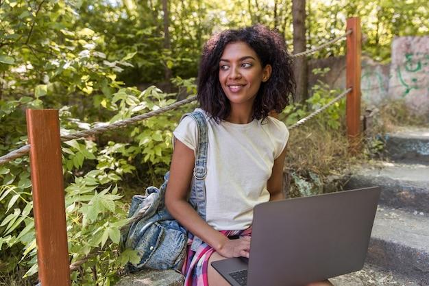 Alegre mulher africana ao ar livre, sentado na escada.