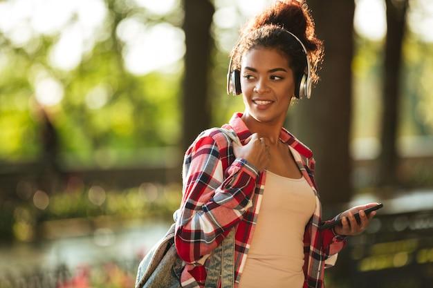 Alegre mulher africana jovem caminhando ao ar livre