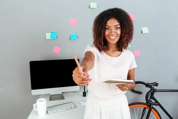 Alegre mulher africana jovem em pé perto do computador