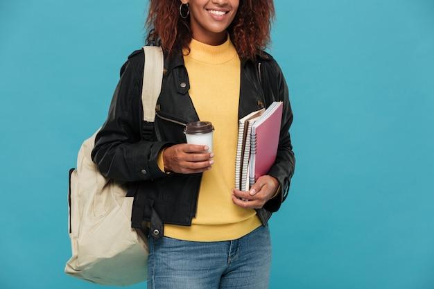 Alegre mulher africana jovem segurando cadernos e café.
