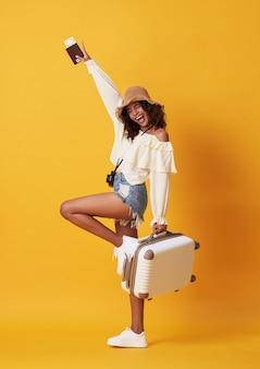 Alegre mulher africana jovem vestida com roupas de verão, segurando o passaporte com dinheiro