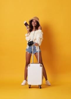 Alegre mulher africana jovem vestida com roupas de verão, segurando um passaporte com dinheiro