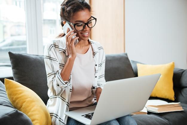 Alegre mulher africana usando laptop sentado na biblioteca