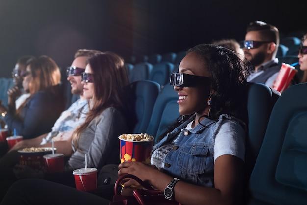 Alegre mulher africana usando óculos 3d enquanto assiste a um filme no cinema