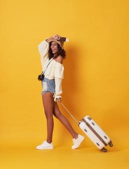 Alegre mulher africana vestida com roupas de verão, segurando o passaporte com dinheiro em pé com uma mala