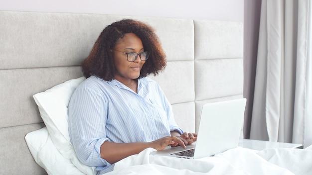 Alegre mulher afro-americana com óculos trabalha em um laptop em casa, em conexão com a quarentena de coronavírus