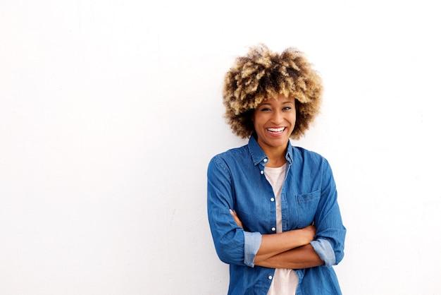 Alegre mulher afro-americana com os braços cruzados em fundo branco