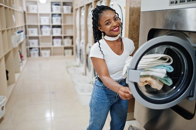 Alegre mulher afro-americana com toalhas nas mãos perto da máquina de lavar roupa na lavanderia de auto-serviço.