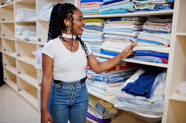 Alegre mulher afro-americana ficar perto de prateleiras com toalhas na lavanderia self-service.