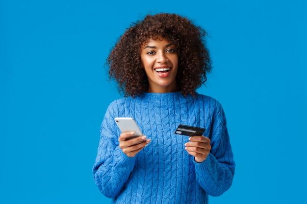 Alegre mulher afro-americana sorridente bonita compra on-line, compras durante descontos temporada de férias, sorrindo, segurando o smartphone e cartão de crédito, em pé azul