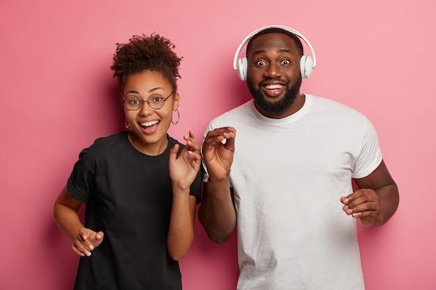 Alegre mulher afro em espetáculos redondos e seu namorado dançam e ouvem música, divirta-se na festa, sorrisos largos, isolados na parede rosa.