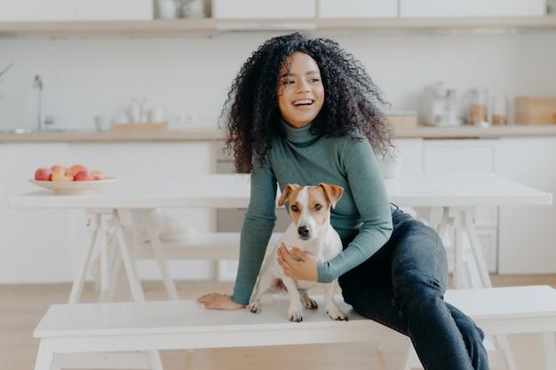 Alegre mulher afro senta-se no banco branco, juntamente com o cão