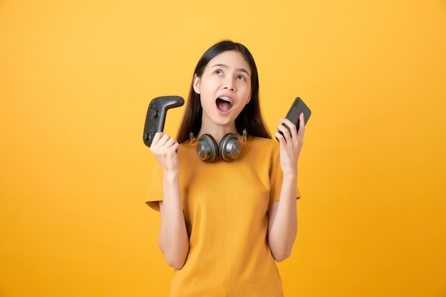 Alegre mulher asiática bonita camiseta casual amarela e jogando videogame usando joysticks com fones de ouvido e smartphone