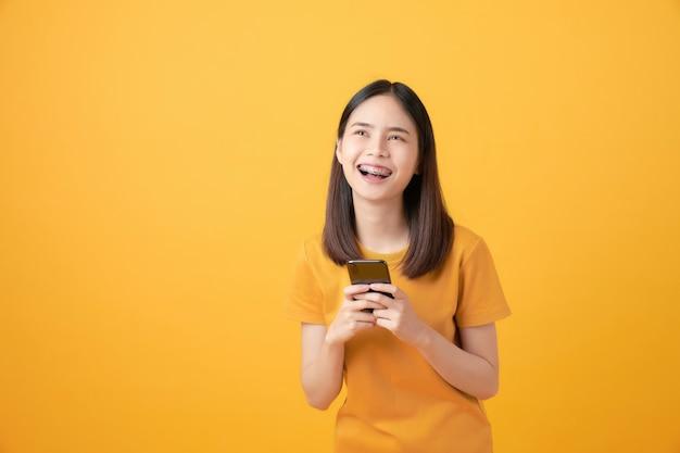 Alegre mulher asiática bonita segurando smartphone