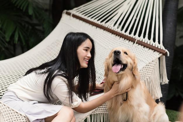 Alegre mulher asiática brincando com seu cachorro golden retriever no jardim em casa