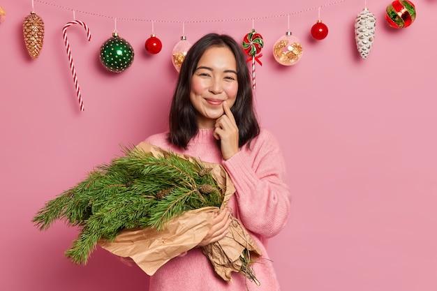 Alegre mulher asiática com ruge bochechas sorri suavemente mantém o dedo perto dos lábios segura buquê feito de árvore do abeto perene se prepara para a celebração do feriado, aproveita o tempo em casa. conceito de feliz natal