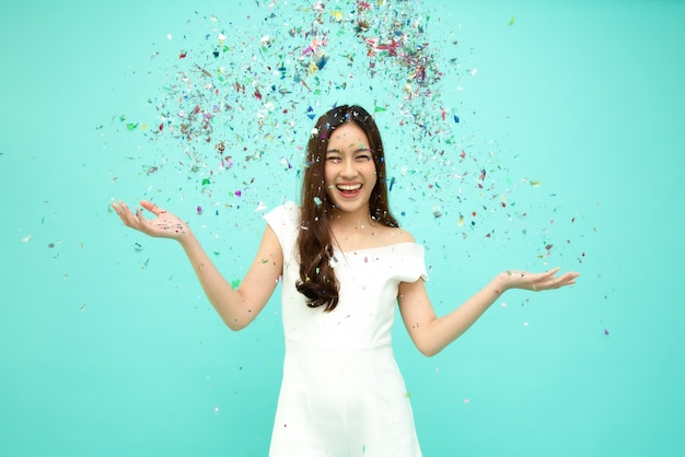 Alegre mulher asiática jovem comemorando com confetes coloridos