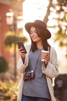 Alegre mulher asiática no chapéu preto e casaco de lã, verificando notícias no celular enquanto bebe café na rua