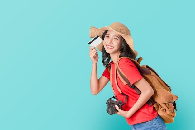 Alegre mulher asiática segurando o cartão de crédito pronto para viajar