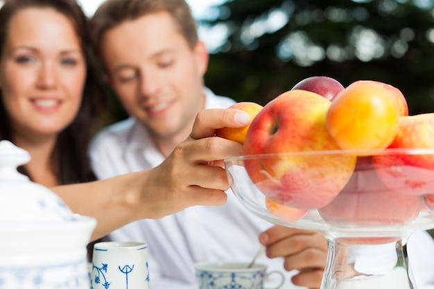 Alegre mulher atingindo através da mesa de café para uma tigela de frutas