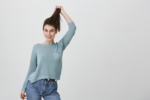 Alegre mulher atraente, puxando o cabelo, anunciar produtos capilares