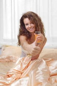 Alegre mulher bebendo suco de laranja, sentado em sua cama em casa