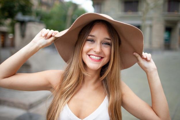 Alegre mulher bonita animada segurando a borda do chapéu