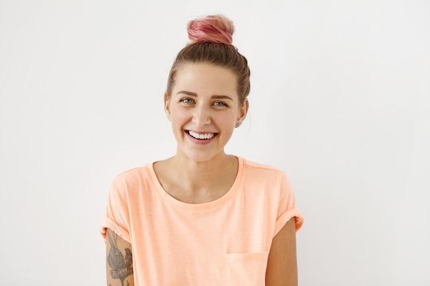 Alegre mulher bonita com nó de cabelo, vestindo camiseta casual, sorrindo agradavelmente, demonstrando dentes perfeitos brancos