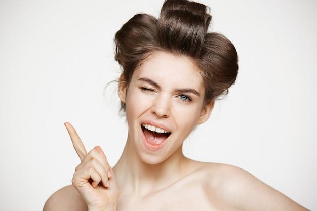 Alegre mulher bonita em rolos de cabelo, sorrindo com a boca aberta piscando.