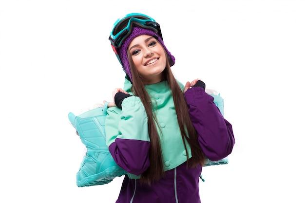 Alegre mulher bonita jovem no casaco de esqui roxo e óculos de proteção