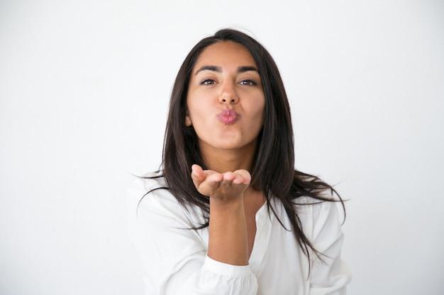 Alegre mulher bonita mandando beijo de ar em