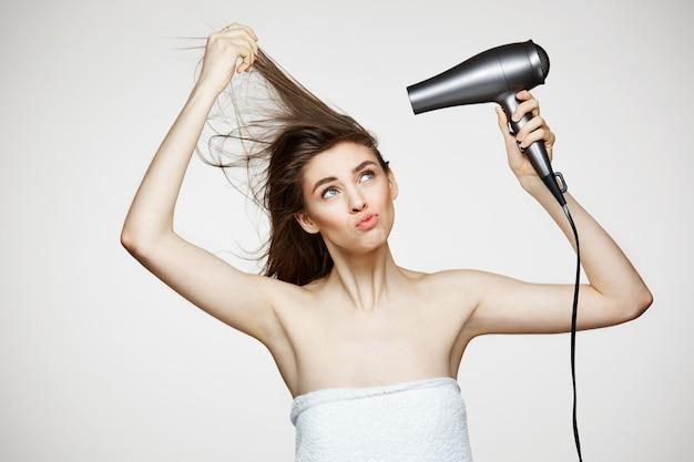 Alegre mulher bonita toalha sorrindo rindo cantando com secador de cabelo fazendo careta. spa de beleza e cosmetologia.