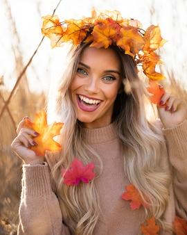 Alegre mulher bonita usando maple folhas grinalda se divertindo ao ar livre