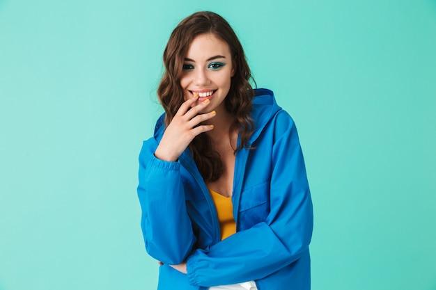 Alegre mulher bonita vestindo capa de chuva ou jaqueta sorrindo para a câmera