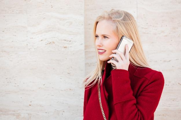 Alegre mulher caucasiana jovem caminhando ao ar livre, falando por telefone