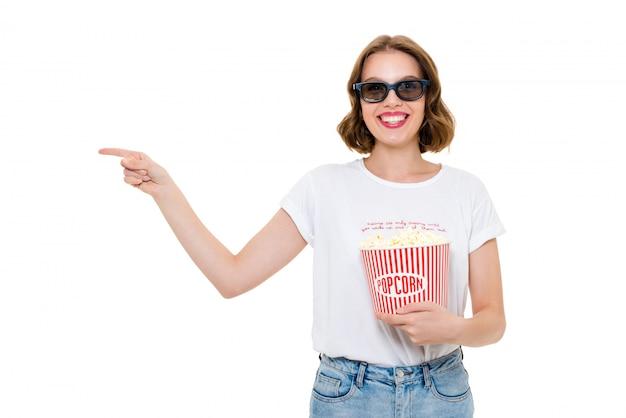Alegre mulher caucasiana segurando pipoca assistir filme e apontando.