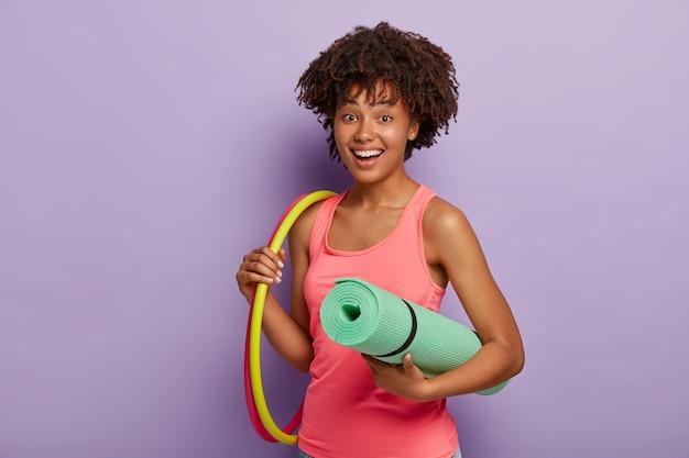 Alegre mulher com cabelo culy desportivo segura tapete enrolado, dois bambolês, veste colete rosa, faz exercício no ginásio