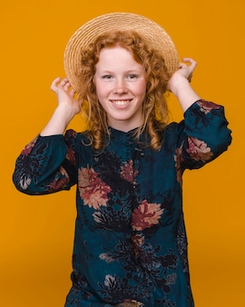 Alegre mulher com cabelo ruivo em estúdio com fundo colorido